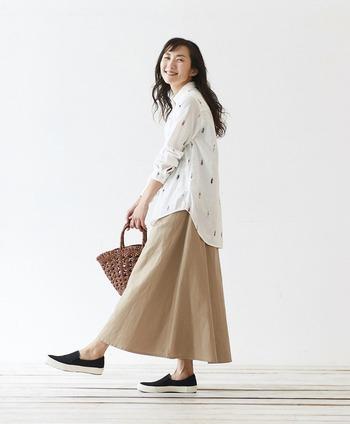 白いシャツとベージュのスカート、ナチュラルさんにお馴染みのカラーリングを黒のスリッポンで引き締めたコーディネートです。すっきりシルエットのスリッポンを合わせれば、ゆるっとしたファッションも品よくまとまります。