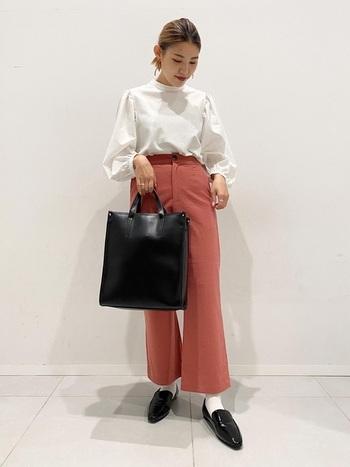 フレアシルエットのピンク色のパンツにボリュームスリーブブラウス。華やかなよそゆきスタイルを引き締めるのは、よく手入れされた革のバッグ&シューズ。白い靴下と合わせたところも巧みです。