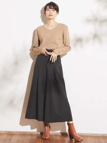 ベージュカラーのシンプルなロンTに、黒のロングスカートを合わせたコーディネート。ベーシックアイテム同士の組み合わせですが、シンプルになり過ぎないよう大ぶりのアクセサリーをプラスしています。足元はブラウンの足袋ブーツで、こなれた雰囲気に。
