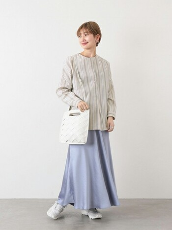 マルチカラーのストライプブラウスに、ブルーのフレアスカートを合わせたコーディネート。あえてブラウスをタックインしないスタイリングで、今っぽい大人女子コーデに仕上げています。白のバッグとシューズで、爽やかな明るめカラーをプラスしているのもポイント。