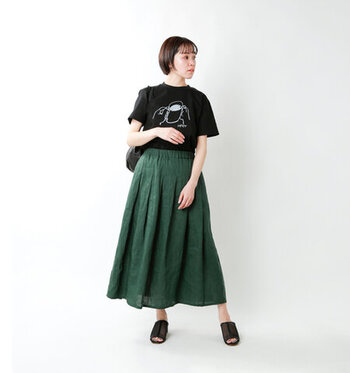 黒のトップスや小物に、グリーンのスカートを差し色にしたスタイリング。程よいボリュームのリネン100%のスカートが夏らしく涼やかで、黒いTシャツの圧迫感を感じないおしゃれな着こなしです。