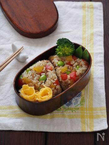 赤や黄色のパプリカに枝豆の緑……カラフルな見た目がかわいいカレー味のおにぎりです。野菜もお肉もバランスよく摂れるレシピ。お子様のお弁当にもぴったりです。