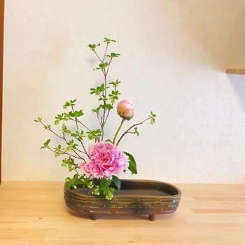 芍薬と「ドウダンツツジ」を合わせた生け花。花器の片側に寄せたアレンジがとても上品です。  すらりと伸びた枝のラインが美しい「ドウダンツツジ」は生け花にも使えるんですね。