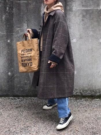ゆったりとしたチェックコートにパーカーを重ねたスタイリング。カジュアルなデニムスタイルも、トラッド風の冬コートと合わせることでこなれた印象に。