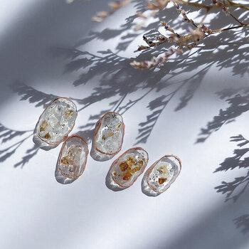 ドライフラワーと天然石が閉じ込められた、アートのようなデザインのネイルです。ゴールドの縁取りが絶妙で、透明感と爽やかさに知的な雰囲気が足された見事な透け感ネイルに感動です!