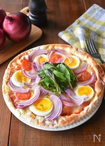 ピザの具材は放射線状に順番を決めて並べるのがコツです。さらに野菜などで形が左右対称でないものは写真のように同じ方向に追いかけていくように並べるときれいです。 バジルやパセリなどの緑のものを添えることでお店のような仕上がりに。
