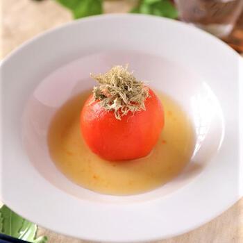 冷凍トマトの丸ごと出汁浸しです。シンプルなフォルムがとても美しいですね。  トマトを冷凍すると、細胞が壊れて、味が染み込みやすくなります。漬け汁に4時間ほどつけておくと、ゆっくりと解凍しながら味がじんわりと染み込んで、まるで高級料亭のようなお味に。トッピングのとろろ昆布はこんもりとのせると、上品です。