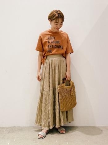 たっぷりとしたティアードスカートをロゴTシャツでほどよくカジュアルダウン。全体を同系色でまとめ、ナチュラルかわいいコーディネートになっています。Tシャツの裾をラフにスカートインしたところもおしゃれ◎