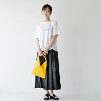 白のロゴTシャツとAラインスカートを合わせ、シックなスカートスタイルに。ほどよくゆるいシルエットが、気負わないリラックス感を演出しています。アクセントにしたイエローのバッグもGOOD!