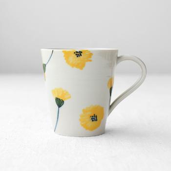 九谷焼の「陶房ななかまど」のたんぽぽのマグカップ。テーブルに優しく映える花模様が印象的です。風に舞うようなゆったりとした動きも感じられます。