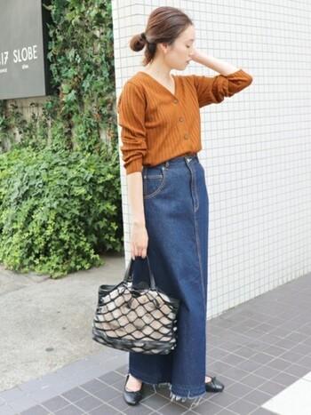 ブルーデニムのロングスカートにオレンジのVネックカーディガンをトップス風に着こなしたスタイリング。袖をたくし上げて子なれ感をプラス。トップスインで、スタイルアップが狙えます。