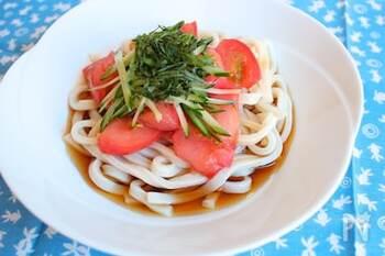 冷凍トマトをトッピングしたぶっかけ冷やしうどん。  ざく切りトマトで作った冷凍トマトは、ジップロックなどの保存袋に平らにして冷凍しておけば、必要な分だけ、パキッと折って使うことができます。冷凍トマトをそのままのせて、麺を冷やすことができるため、うどんをレンジ加熱した後に、水で締める必要がありません。思い立ったらすぐに作れるスピードレシピです。