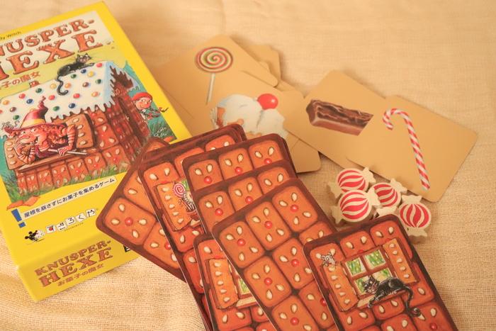 箱を開けた瞬間、「わあ!」と歓喜の声が出てしまいそう。キャンディー、ケーキなどおいしそうなお菓子がプリントされたカード、そしてお菓子でできた壁やドアのカード、キャンディーのコマが。なお、このゲーム、カード類が入っていた箱も大切な道具になります。