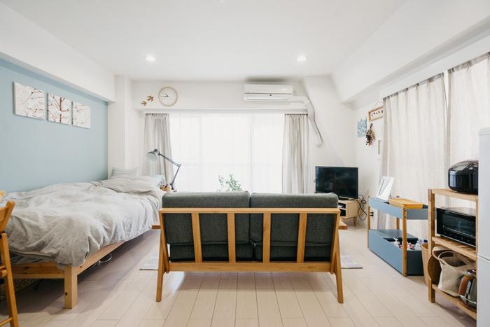 少し広めで、ベッドもソファも置けるゆとりのあるワンルーム。ソファを窓に向かって配置することで、キッチンとくつろぎスペースをゾーニングしています。ベッドもソファも脚に高さがある分、床が見えてすっきりした印象に。
