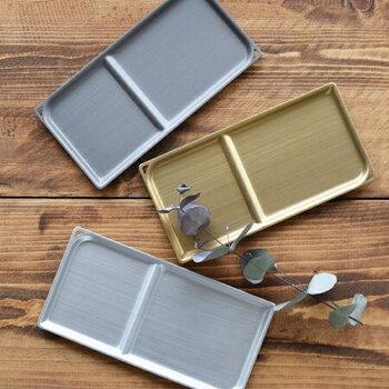 日本製の長方形のアルミトレイ。アルマイト加工で変色などを防ぎ、お手入れしやすく耐久性のある製品にしています。仕切りがあるので、おやつとカップを乗せて使えます。