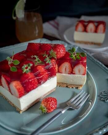 牛乳パックを型にした四角いレアチーズケーキ。白いチーズの層と、透明なゼリーに閉じ込めた真っ赤なイチゴとの対比がきれいです。