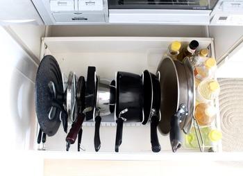 フライパンや鍋は横に重ねるより立てて収納する方が取り出しやすくなります。専用スタンドを使えば、シンク下でも引き出しでも縦置き収納できますよ。