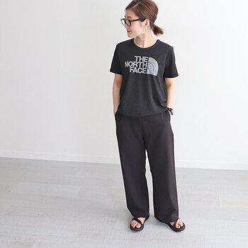 黒のロゴTシャツに、黒のゆるパンツを合わせたコーディネートです。足元はサンダルで、ラフな印象の着こなしにまとめています。全体的にリラックス感のあるアイテムですが、全身ブラックにするだけでスタイリッシュな雰囲気になりますね。
