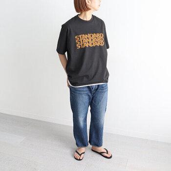 黒のロゴTシャツに、デニムパンツを合わせたスタンダードなコーディネート。Tシャツの裾からインナーをチラ見せすることで、ベーシックな着こなしにトレンド感のあるアクセントをプラスしています。足元はサンダルで、これからの季節にぴったりなラフさをアピール。
