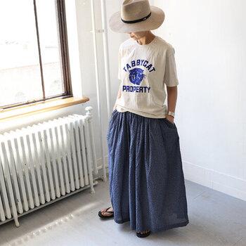 白のロゴTシャツに、青のアニマル柄スカートを合わせたコーディネートです。Tシャツのロゴとスカートの色を合わせているので、柄スカートが浮かずにスッキリと着こなせています。ストロー素材のハットやサンダルで、季節感を演出。