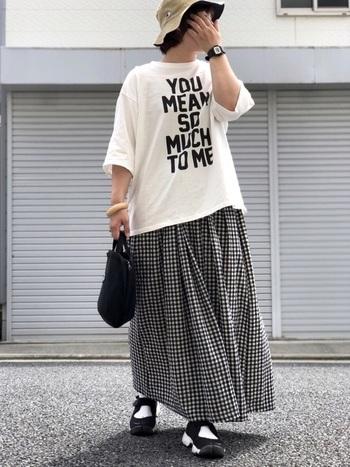 白のロゴTシャツに、チェック柄のフレアスカートを合わせたコーディネートです。カジュアルなロゴTシャツに、甘さのあるギンガムチェックスカートが、程よいミックスコーデに。足元はごつめのサンダルスニーカーで、甘辛のバランスをとっています。全体がモノトーンカラーで揃っているので、ミックススタイルにも違和感がありませんね。
