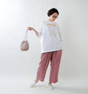 白のロゴTシャツに、ピンクのワイドパンツを合わせたコーディネートです。白ベースのロゴTシャツは、どんなカラーのボトムスも合わせやすい優秀アイテム。パッと目を引くキレイ色のボトムスを、しっかり主役に見せてくれます。