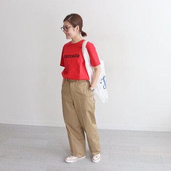 スタンダードなベージュのパンツに、赤のロゴTシャツをタックインしたスタイリング。スニーカーとトートバッグで、とことんカジュアルな着こなしにまとめています。赤×ベージュは相性抜群のカラーリングなので、赤Tシャツを派手見えさせずにスタイリングできますよ。