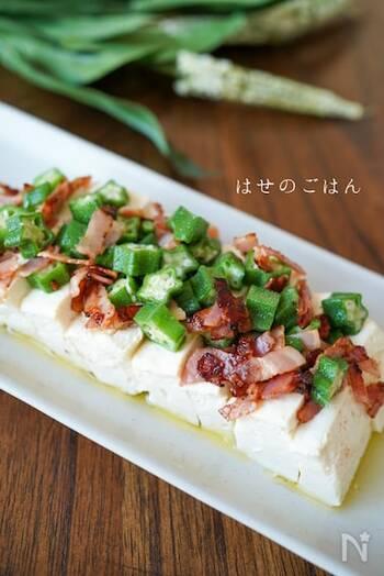オリーブオイルでカリカリ炒めたベーコンがアクセントの冷奴。オクラとベーコンをトッピングして、ニンニク入りのオリーブオイルをかけたら完成。  こちらは木綿豆腐を使用していますが、絹ごし豆腐でも美味しくいただけます。
