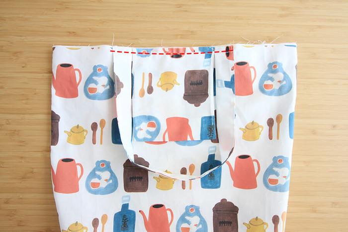 ポケットと持ち手をまち針でとめ、本体に縫いつけます。