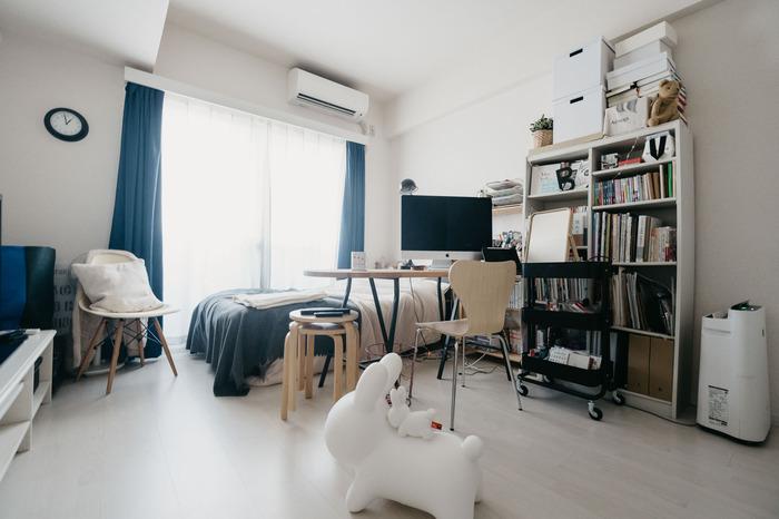 ベッドの横にデスクを横づけすることで、スペースを確保している例です。デスクは仕事、食事、サイドテーブルと多目的に使える大きめサイズをチョイス。明るめの木目にモノトーンで揃えられたインテリアも、すっきりした印象です。