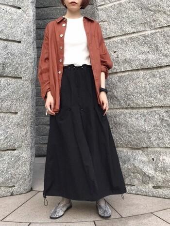 ちょっと個性的なパイソン柄のカンフーシューズを黒のロングスカートの裾から覗かせれば、シンプルな着こなしのちょうどいいアクセントに。