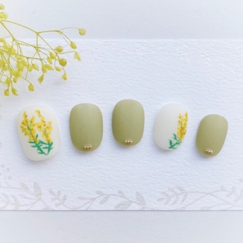 白地いっぱいにミモザの花と、ピスタチオカラーとの組み合わせが美しいネイルデザイン。マット仕上げと小さな3連のスタッズが控えめながら上品な印象に仕上げてくれています。指先に花があると毎日がきっとウキウキで過ごせそう。