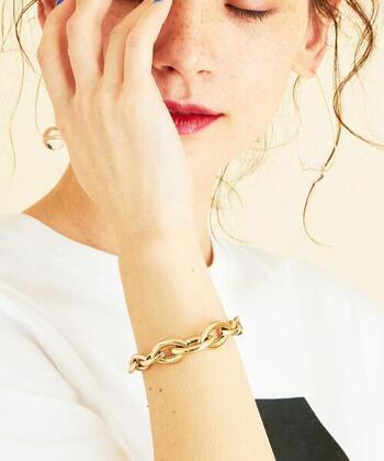 メタリックゴールドの美しい光沢感が、女性らしい印象を与える太めのチェーンブレスレット。ちょっぴりレトロな雰囲気を醸し出すアイテムは、今っぽさをグッと格上げしてくれます。ドレススタイルに合わせて、程よくカジュアルダウンさせても素敵です。
