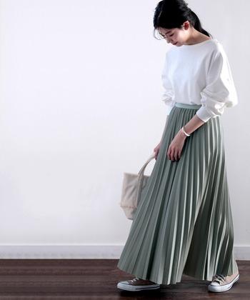 フレアなラインが女性らしい、カーキのプリーツロングスカート。白のゆったりトップスをウエストインして、上下のメリハリとバランス感をしっかり意識したコーディネートです。