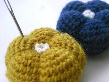 テーブルの上で映えるおしゃれなピンクッションです。ぷっくりとふくらみのある不思議な形は、細編みで球状に編んで綿をつめてから、糸で分割するようにくぼみをつけて作ります。