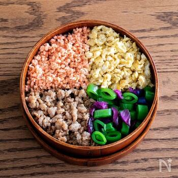 鮭、炒り卵、そぼろと、子供の大好きなおかずをご飯の上に乗せて。緑の部分はお漬物を細かく切ったものが入っています。