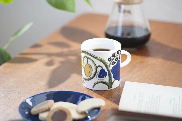 """フィンランド語で""""楽園""""を意味するパラティッシのマグカップ。花や果実が大胆に描かれ、「ARABIA(アラビア)」を代表する人気デザインです。こちらは、パラティッシの定番のカラーマグ。写真は350mlですが、240mlもあります。"""