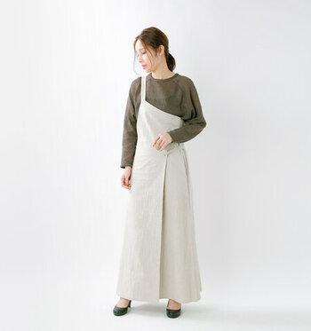 エプロンタイプのワンピースは、ワークウェアの中でも、着るだけでもっとも女性らしさが引き立つアイテムです。ヘアスタイルを女性らしくアップにしたり、バッグなどに華奢なものを選んだりして、上品さをプラスさせましょう。