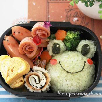 カエルとカタツムリのキャラ弁。カタツムリはソーセージに切れ目を入れてくるっとするだけ。雨の日も楽しく過ごせそうなお弁当ですね。