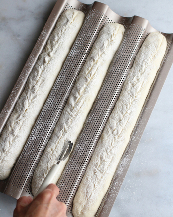 【5】発酵が完了したら軽く表面に粉を振り、斜めに3本のクープを入れる。オーブンは230度に温度を落とし、スチームを5分入れ20分程度焼いたら完成!  <POINT> スチームがない場合は霧吹きでも対応できます。霧吹きやスチーム機能を使うことで、表面がよりバリッとしたバゲットに仕上がりますよ。