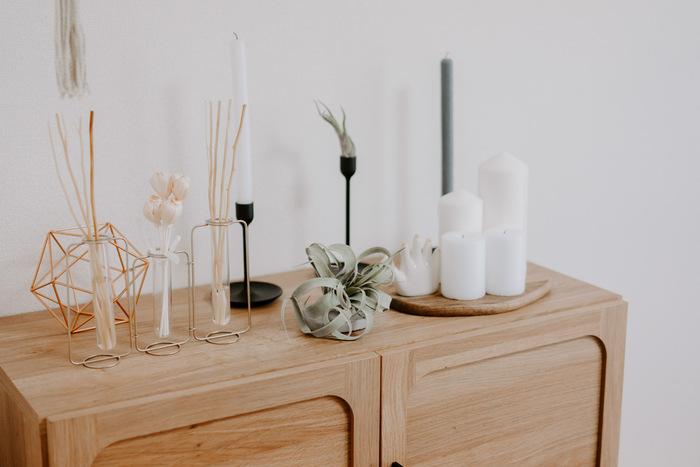 キャンドルやアロマスティックなどの小さな雑貨を並べるだけでも、飾り棚として素敵な演出空間に。  しかし、金属やガラスなどの無機質なものだけを飾ると、少しばかり物足りなさを感じてしまうもの。そこへ、植物をプラスすると温かみのある雰囲気が生まれますよ。  飾る植物によっても、与える印象はさまざま。フレッシュな印象を与えたいなら、生き生きとしたグリーンを。アンティークっぽさを加えたいなら、ドライフラワーを。存在感のあるエアープランツなら、都会的で知的な印象のお部屋をつくることができます。
