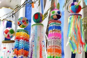 七夕まつりなどでおなじみの、風船やくす玉に色とりどりの紙などを貼り付けた華やかな「吹き流し」。古来の七夕の行事で五色の糸を針に通し、お供えしていたものを、今では五色の紙に置き換えており、裁縫が上達するよう、願いが込められた飾りです。