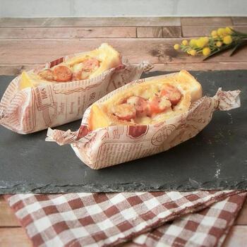 食パンに切れ目を入れてポケットを作り、レトルトカレーやウインナーを詰めたらチーズをのせて焼くだけ。写真のようにクッキングシートで包んでかわいいポケットサンドのできあがり。