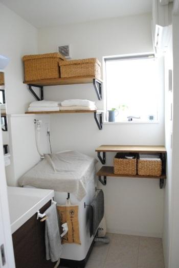 洗濯機上のスペースにウォールシェルフを取りつけて収納に。タオルや洗濯洗剤などをすっきり収納できます。また、こちらでは洗濯機横にもウォールシェルフをプラス。入浴時の着替え置きとしても便利ですね。