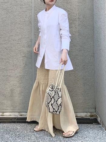 襟元のつまったスタンドカラーシャツにベージュのマーメイドスカートで、フェミニンなシルエットに。シャツは後ろ身頃の方が少し丈が長くなっていて、ひらりと翻る雰囲気がとてもお洒落です。  マキシ丈のスカートからちらりとのぞくサンダルの素足が、こなれ感をプラス。シャツの真面目さを、絶妙に軽くしてくれますね。