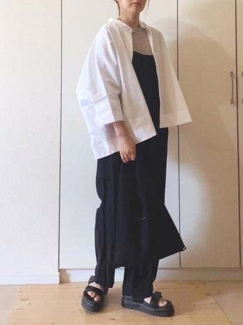 黒のサロペットに羽織り風に合わせたドルマンスリーブシャツ。  ボタンを開けたら、すこし抜き襟気味に着るとよりこなれた感じに。ボリュームのある黒のサンダルで、トップスの丸みのあるシルエットとのバランスをとっています。袖が七分丈なので、羽織りにしても軽やかですね。