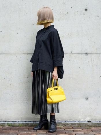 きりりとクールなブラックのドルマンスリーブシャツに、箔プリントプリーツスカートを合わせるというおしゃれ上級者のコーデ。  インパクトの大きい個性派スカートも、端正な表情のドルマンスリーブシャツと一緒なら、落ち着いて見えます。差し色にした黄色のバッグが効いています。