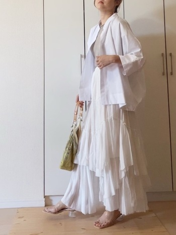 たっぷりとしたティアードスカートに羽織り風に合わせたドルマンスリーブシャツ。  すこし色味の違うトップスとスカートの白が重なり、立体的なコーデに。ボリューム感のあるトップス&ボトムスなので、足もとはクリアのヒールサンダルですっきりと。お出かけにも使えるきれいめコーデです。