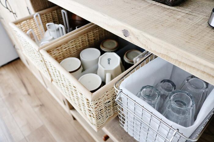 ワイヤーバスケットに不織布のインナーケースを入れてグラス収納に。インナーケースがあれば、ワイヤー製でもグラスに傷が付く心配がなく、ホコリ対策にもなりますね。隣の天然素材のバスケットにはマグカップを収納♪