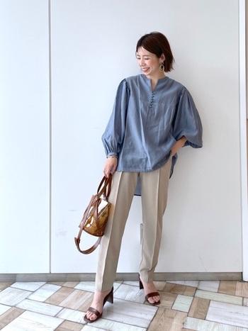 透け感のあるくすみブルーのシャツが爽やか。センタープレスされたテーパードパンツと合わせて大人のきれいめコーデに。でもバルーン袖で女性らしさは忘れない。ブラウンで揃えた小物が全体のアクセントになっています。